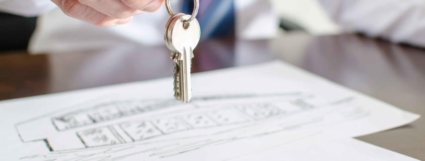 Estate agent holding house keys over a contract