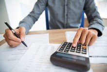 Close-up of male hands using calculator to examine report. Unrecognizable accountant counting profit. Businessman analyzing documents. Paperwork concept