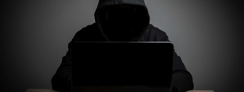 Hacker work front of his laptop computer with dark face.
