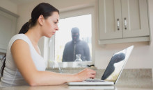 Young woman seeing reflection of robber in laptop screen