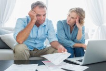 Worried couple using their laptop to pay their bills at home in the living room