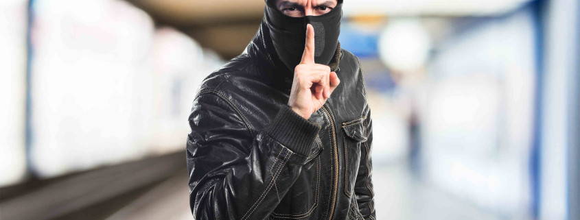 Robber making silence gesture